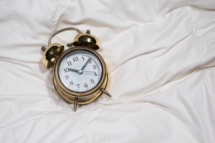 golden alarm bell clock on white bed sheet Bell Gold Hour Lifestyle Moment Alarm Clock Bed Bedroom Clock Clock Face Day High Angle View Indoors  Management Minute Hand No People Old-fashioned Precius Retro Styled Second Sheet Sleeping Time Wakeup White