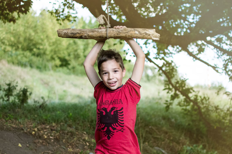 Portrait of happy boy playing with wooden swing
