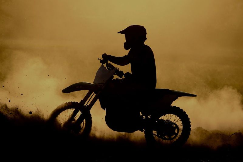 Silhouette man riding motorcycle against sky during sunset