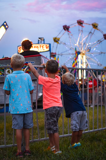 carnival Amusement Park Amusement Park Ride Arts Culture And Entertainment Boys Casual Clothing Childhood Day Elementary Age Enjoyment Ferris Wheel Full Length Fun Girls Grass Leisure Activity Lifestyles Outdoors People Real People Rear View Sky Standing Togetherness
