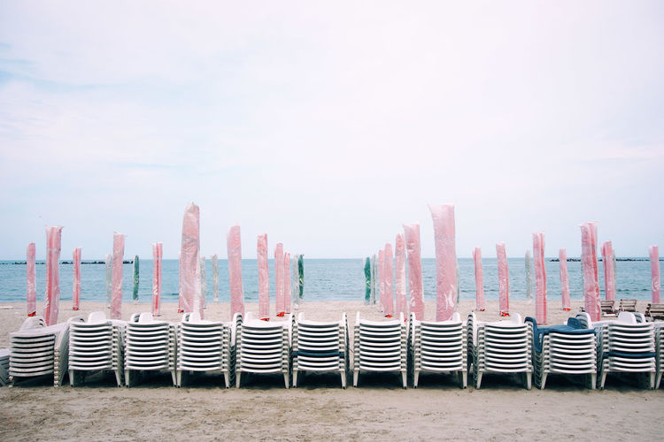 Chairs With Parasols At Beach Against Sky