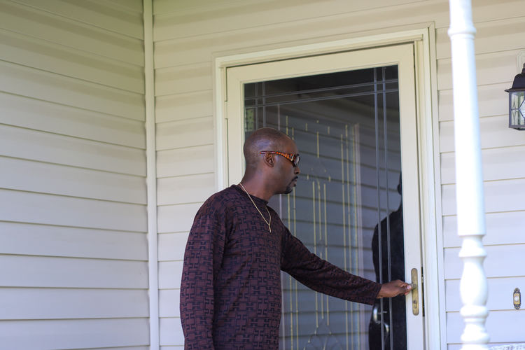 A portrait of an african-american man standing in front of a door and feeling sad