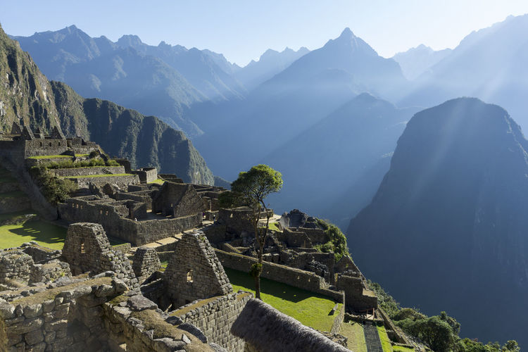 High angle view of old ruins on mountains against sky during sunny day