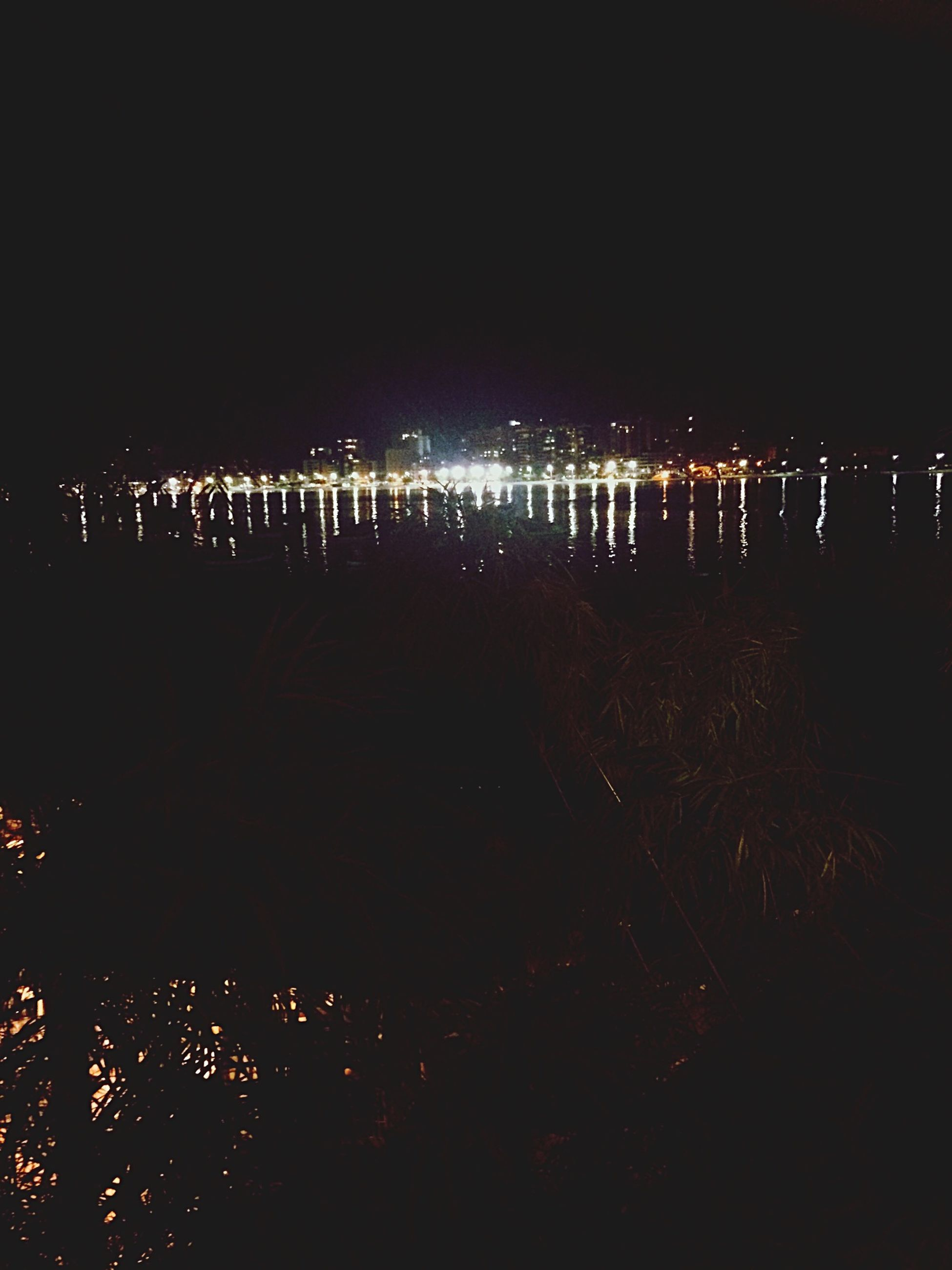 night, illuminated, water, sea, silhouette, beach, dark, sky, in a row, outdoors, nature, no people, shore, city, reflection, copy space, dusk, built structure, light - natural phenomenon, incidental people