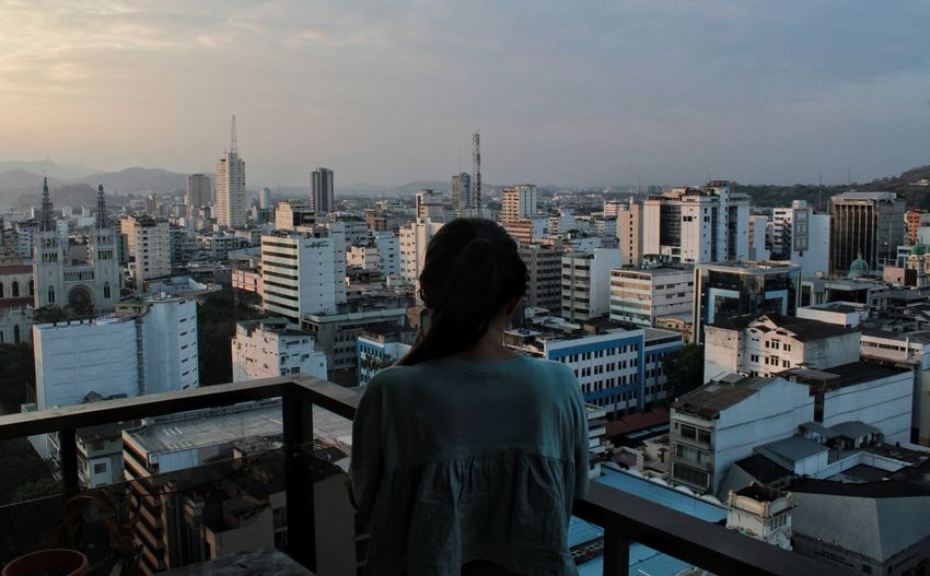 Rear view of woman standing at balcony against cityscape