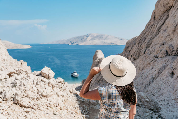 Rear view of woman in summer clothes and sun hat looking at spectacular view and sea coastline.