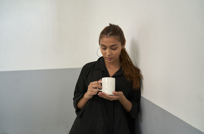 Young woman holding coffee cup against wall