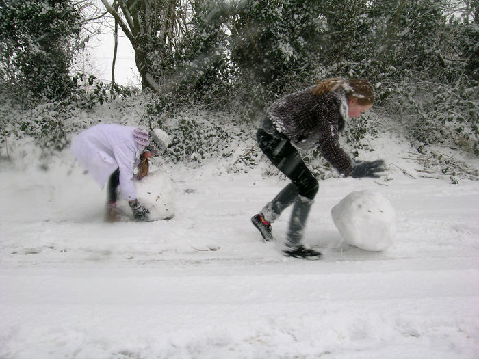 Two girls rolling large snowballs