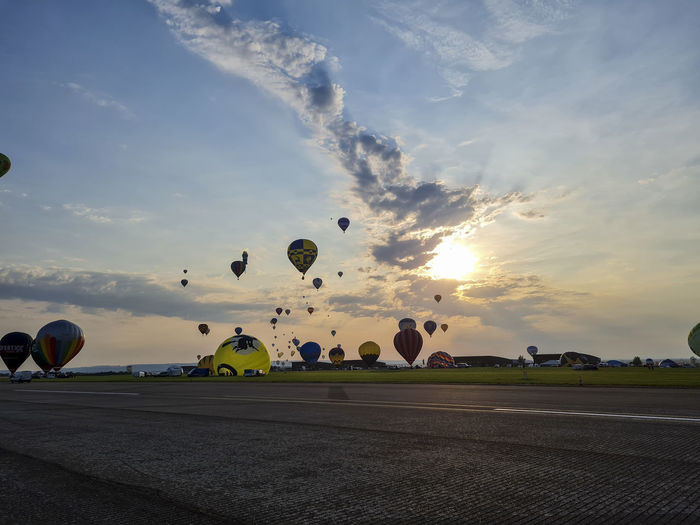 View of hot air balloons flying against sky during sunset
