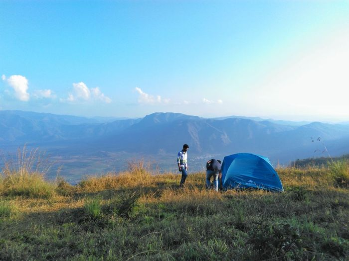 Setting a tent camp on a hill top. Blue Nature Adventure Mountain Rear View Hiking Adults Only Sport Landscape Outdoors Adult Healthy Lifestyle Travel Destinations Beauty In Nature Leisure Activity People Vacations Grass Scenics Kerala Travel Vacations Nature Day Kumily