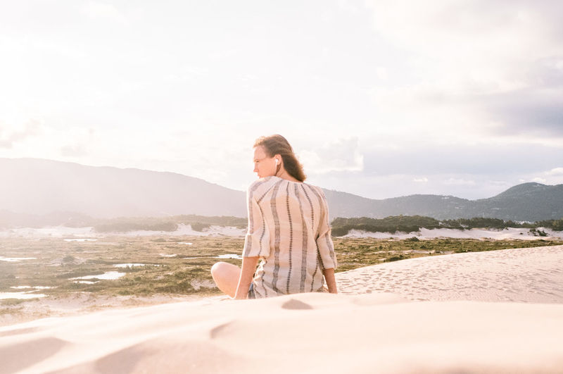 Rear view of woman sitting at sandy beach against sky