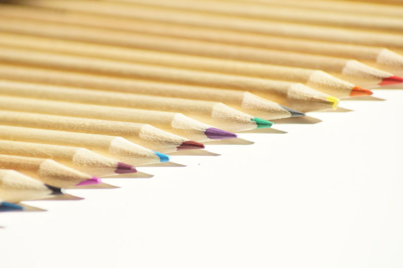 Color pencils arranged on white background