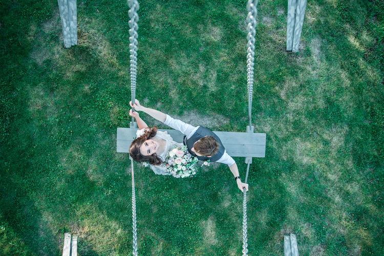 Bride and groom standing on swing at park