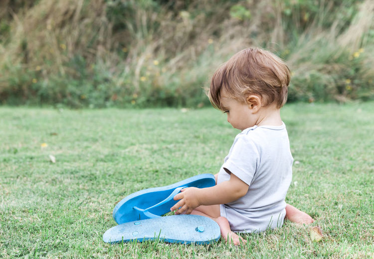 Toddler Girl Holding Slippers While Sitting On Grassy Field