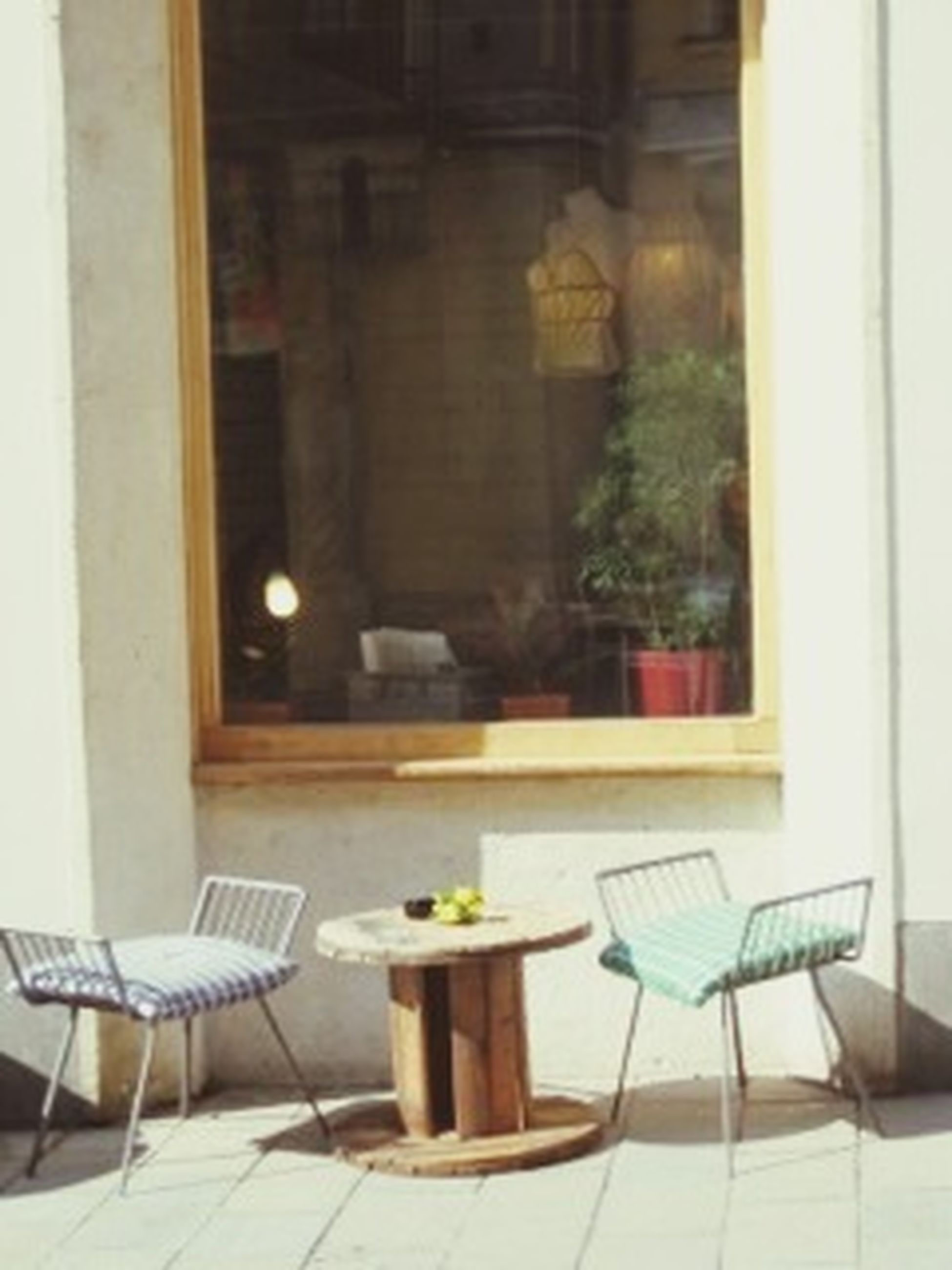 chair, indoors, table, absence, empty, furniture, window, restaurant, potted plant, home interior, dining table, place setting, seat, sidewalk cafe, bench, architecture, vase, living room, relaxation, sofa