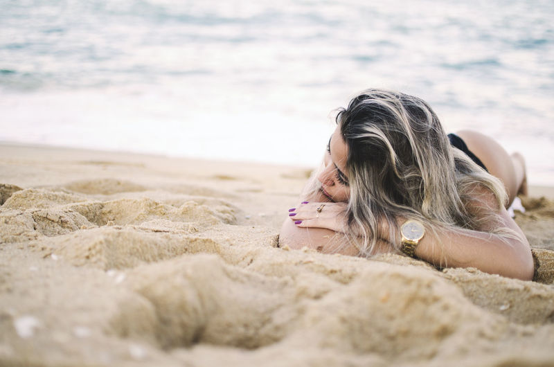Land One Person Beach Lying Down Leisure Activity Sand Hair Long Hair Relaxation Women Lifestyles Hairstyle Nature Day Real People Sea Blond Hair Selective Focus Outdoors Surface Level Beautiful Woman