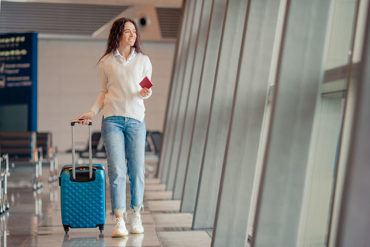 Full length of woman with luggage walking at airport