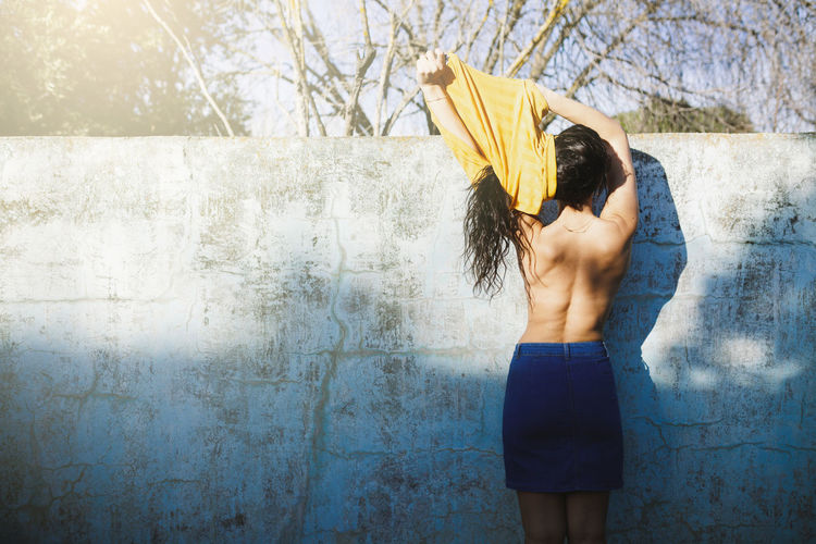 Rear View Of Shirtless Woman Removing Top While Standing Against Wall