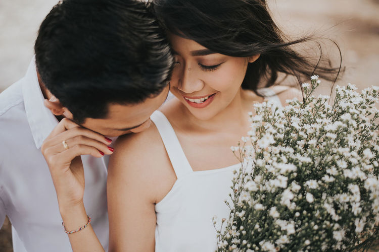 Young Couple With White Flowers Romancing Outdoors