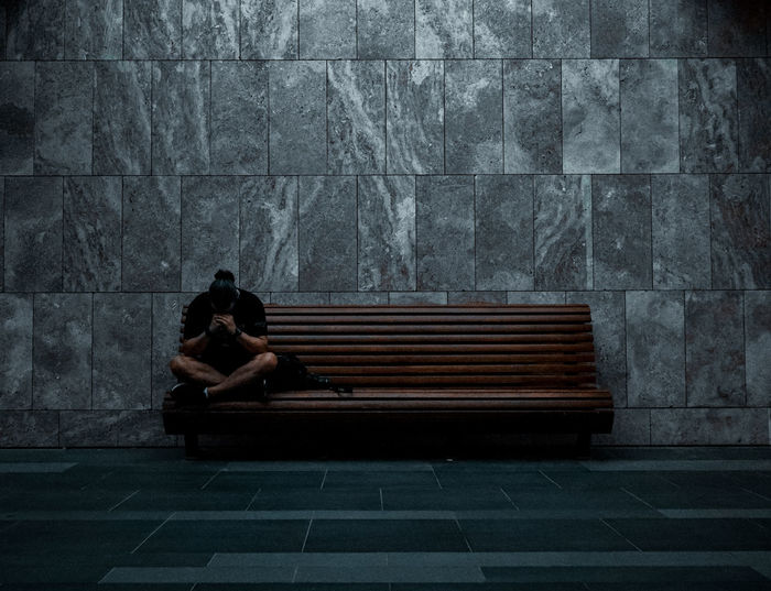 The sad man is sitting on the bench