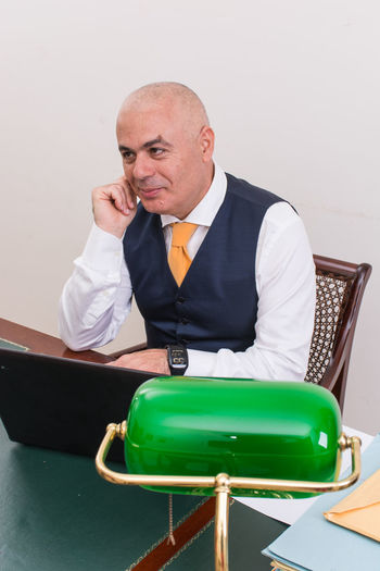 Thoughtful businessman using laptop at desk against white background