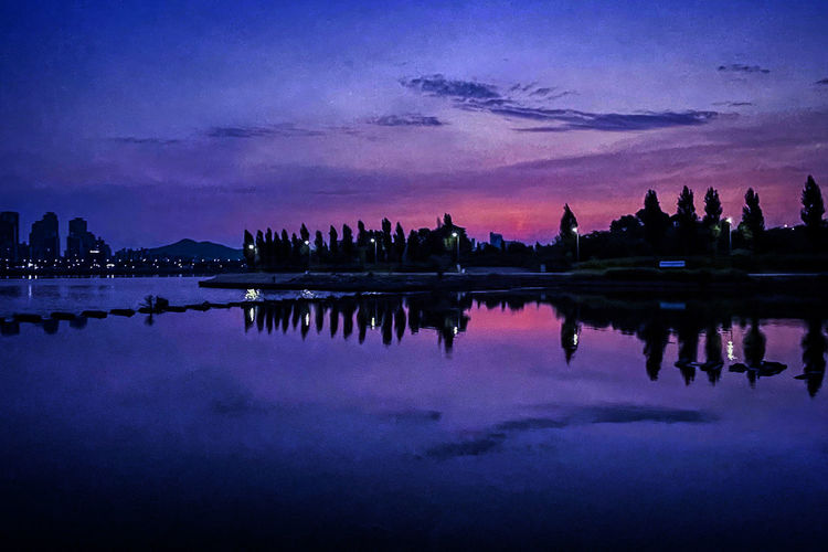 Reflection of silhouette buildings in lake against sky at sunset