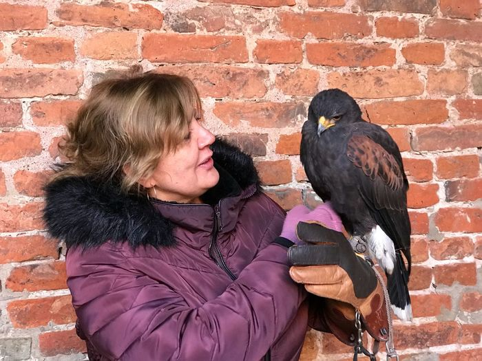 Woman holding bird against brick wall
