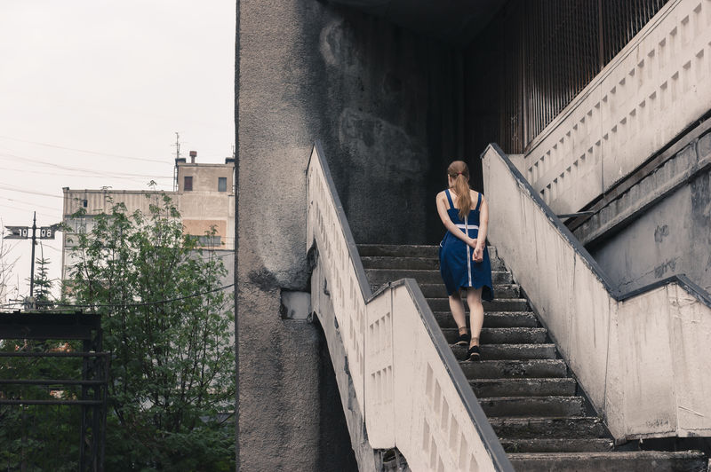 Full length rear view of woman walking on building steps