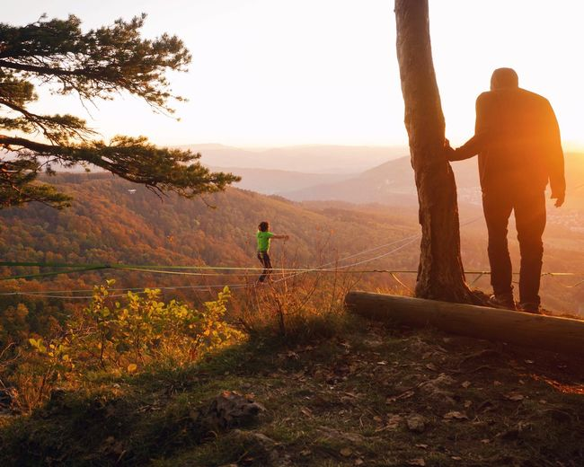 Nature Real People Tree Full Length Beauty In Nature Men Leisure Activity Rear View Two People Standing Scenics The Week On EyeEm Outdoors Sunset Day Adventure Adult Grass Sky Adults Only Lifestyles Lost In The Landscape Slakeline Landscape at Gempen,switzerland