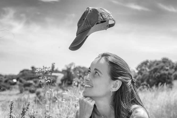 Portrait of young woman looking up towards her levitating cap.