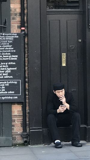 Man sitting on door with text