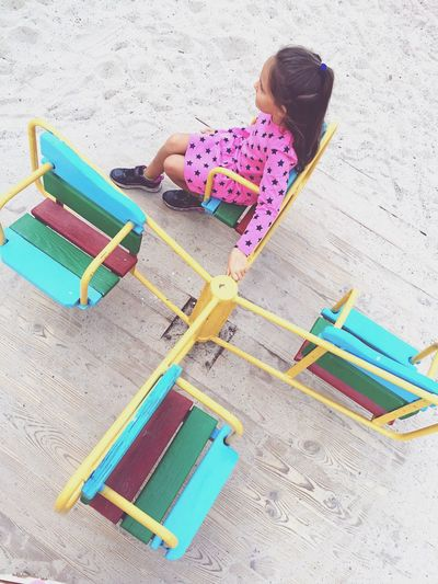 High angle view of girl sitting on merry-go-round in park