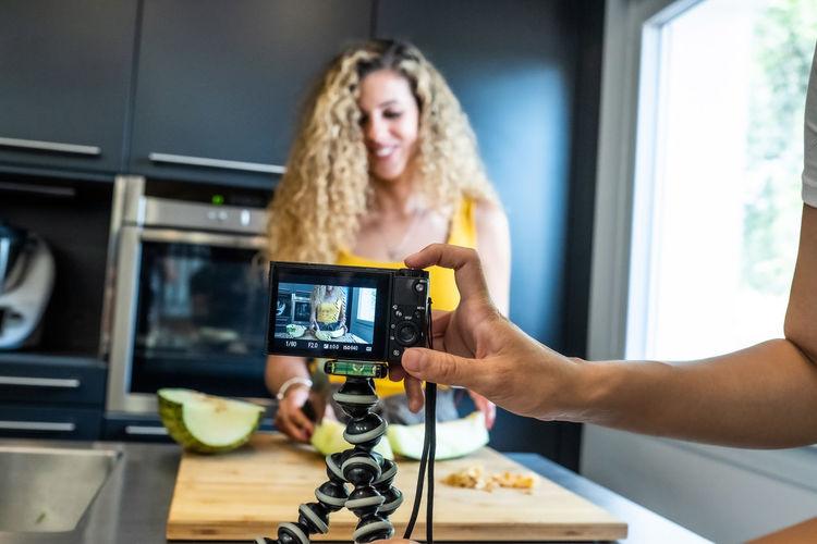 Cropped hand filming woman preparing food