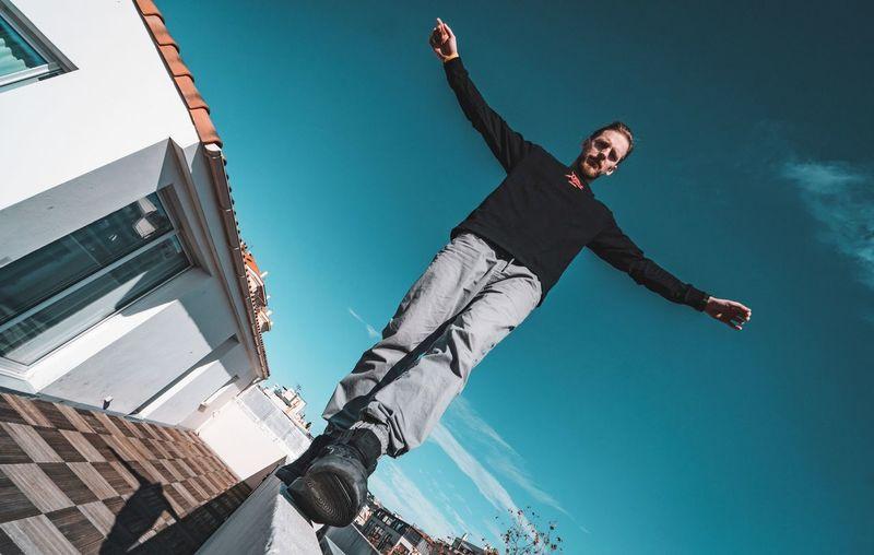 Man walking on retaining wall against sky