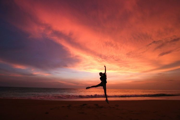 Silhouette person jumping on beach against multi colored cloudy sky