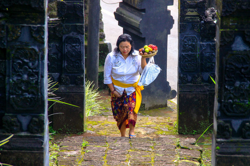 Full length of woman carrying fruits in temple