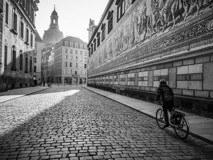 Man riding bicycle on street amidst buildings in city