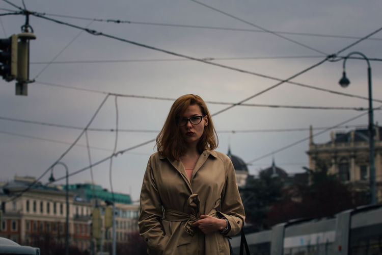 Portrait of young woman standing against sky in city