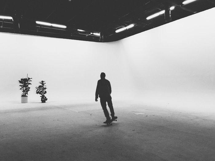 Full Length Of Man Skateboarding In Room