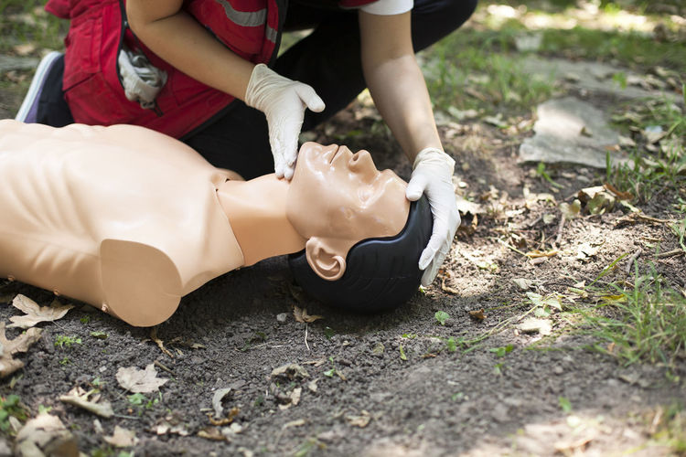 Low section of man practicing cpr on dummy at field