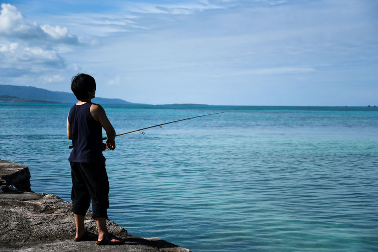 Rear view of man on fishing in sea