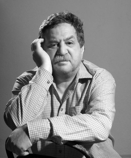 Close-Up Portrait Of Mature Man Sitting On Chair Against Wall
