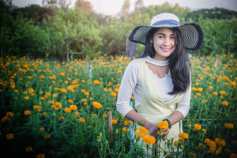 Portrait of smiling young woman wearing hat amidst flowers on field