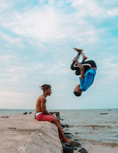 Friends on beach against sky