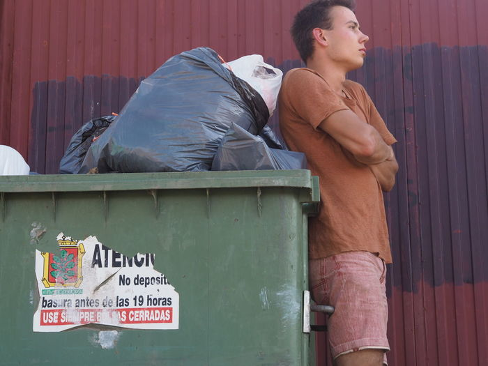 Side view of thoughtful young man standing with arms crossed by garbage bin