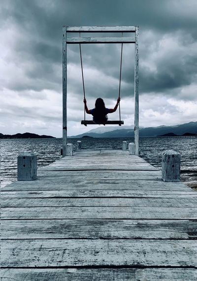 Rear view of woman sitting on swing over pier and sea against sky