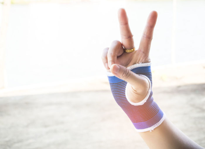 Close-Up Of Hand Showing Peace Sign On Beach