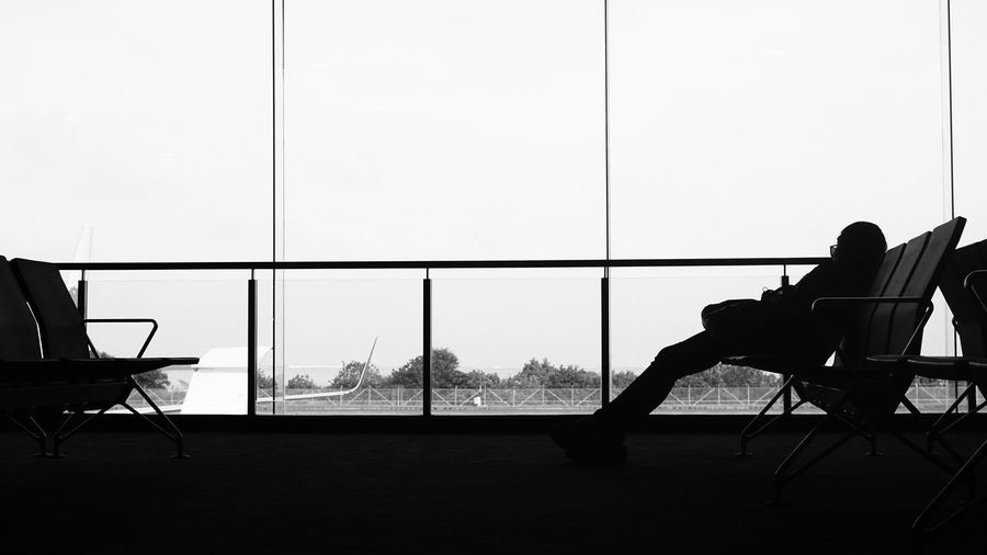 Silhouette person sitting on chair in waiting room