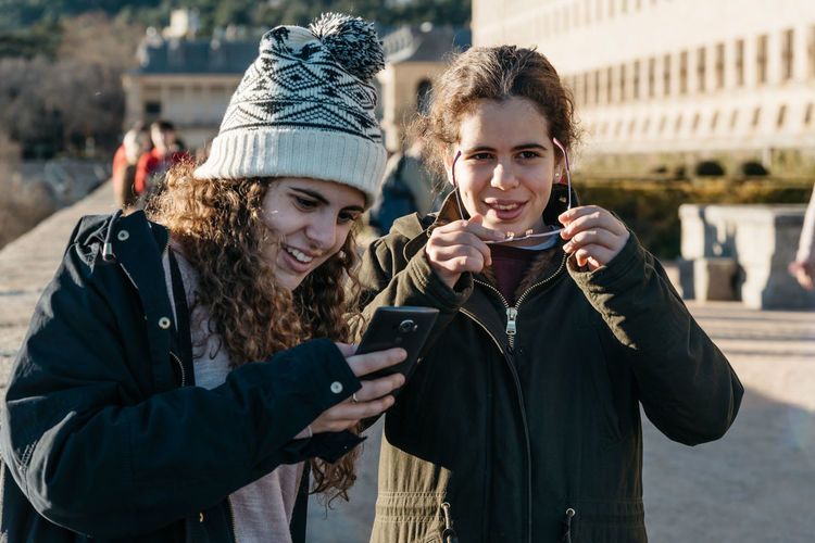 Two young adult women with smart phone. Concept communication El Escorial Young Communication Connection Focus On Foreground Leisure Activity Lifestyles Millennials Mobile Phone Outdoors Photography Themes Portable Information Device Real People Selfie Smart Phone Smiling Standing Technology Togetherness Two People Using Phone Waist Up Wireless Technology Young Adult Young Women