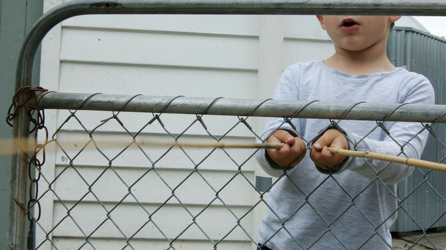 Midsection of boy playing with sticks by chainlink fence